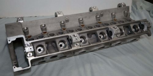 Cylinder head, cam shaft and cam follower pockets